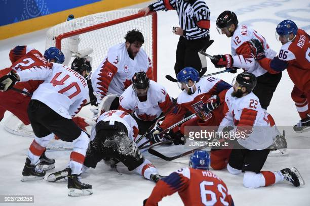 Players fight for the puck in the men's bronze medal ice hockey match between the Czech Republic and Canada during the Pyeongchang 2018 Winter...