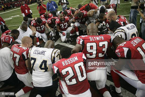Players for Atlanta Falcons and San Diego Chargers huddle together on the field after the game on October 17, 2004 at the Georgia Dome in Atlanta,...