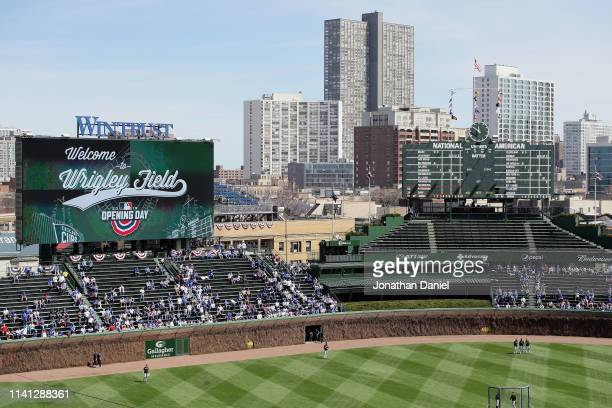 Players for the Chicago Cubs and the Pittsburgh Pirates stand during the National Anthem before the home opening game at Wrigley Field on April 08,...