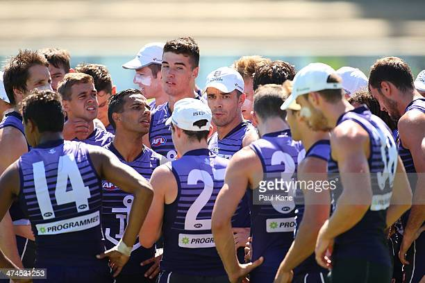 Players form a huddle after warming up during a Fremantle Dockers AFL training session at Fremantle Oval on February 24 2014 in Fremantle Australia
