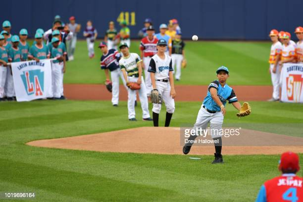 Players from all Little League teams watch as a teammate throws out the first pitch during the MLB Little League Classic before the game between the...