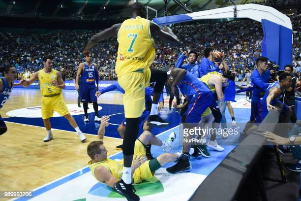 Players from benches run to their teammates who figured in a brawl during the match between Australia and the Philippines for the FIBA Asian...