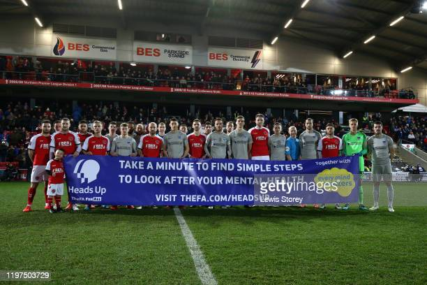 Players from both clubs are seen holding up a banner in support for the Heads Up Campaign prior to the FA Cup Third Round match between Fleetwood...