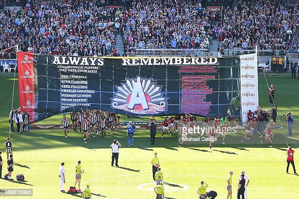Players from both teams run through the Anzac Day banner during the round six AFL match between the Collingwood Magpies and the Essesdon Bombers at...