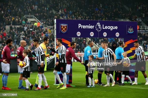 Players from both team's shake hands infront of branding for the This Is Everyones Game campaign prior to the Premier League match between Newcastle...