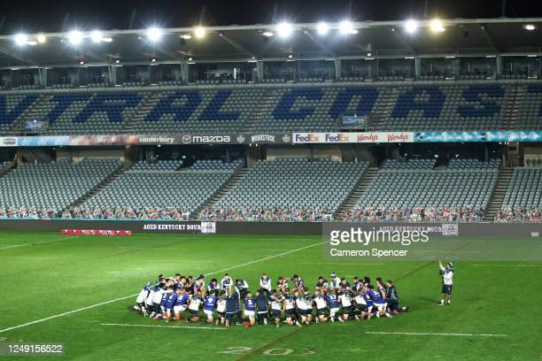 Players from both teams take a knee and huddle together following the round five NRL match between the New Zealand Warriors and the North Queensland...