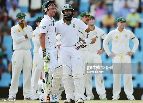 Players from both teams wait for a DRS review which saw Peter Siddle get the wicket of Hashim Amla of South Africa during day two of the First Test...