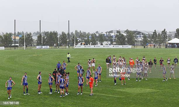 Players from both teams walk off after the game was called off due to the rain during the AFL NAB Cup match between the North Melbourne Kangaroos and...