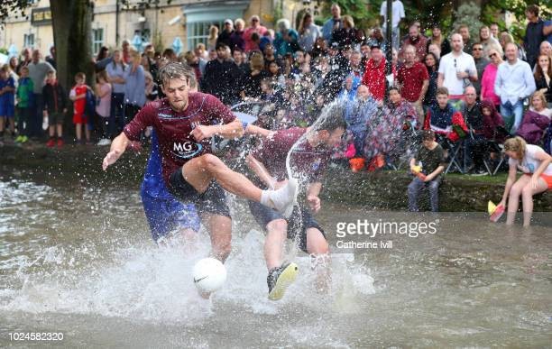Players from Bourton Rovers compete against each other during the annual BourtonontheWater Football Match played on the River Windrush on August 27...