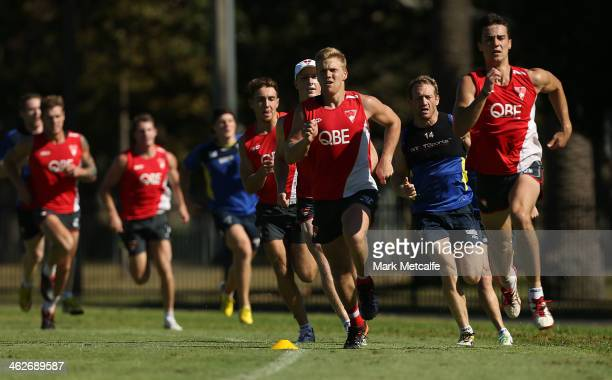 Players from English Super League club Warrington Wolves and Sydney Swans train together during a Sydney Swans AFL preseason training session at...