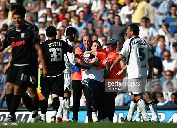 Players from Leeds United and Ipswich Town attempt to constrain a fan who ran onto the pitch during the CocaCola Championship match between Leeds...