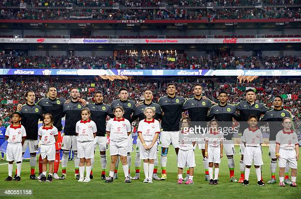 Players from Mexico stand arm in arm for the national anthem before the 2015 CONCACAF Gold Cup group C match against Guatemala at University of...
