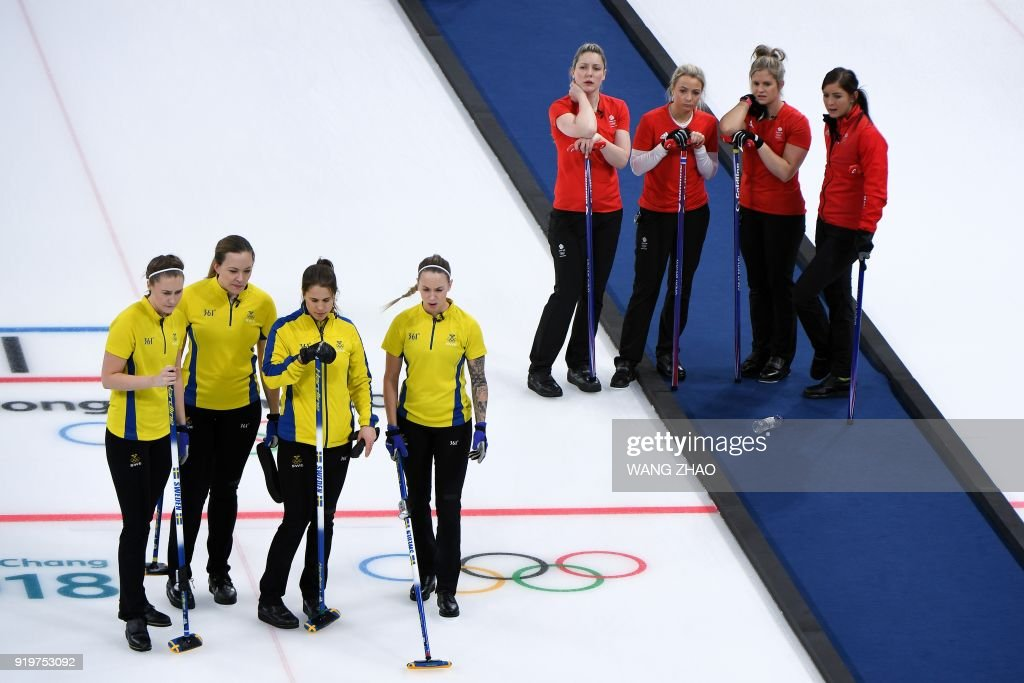 Players from Sweden (L) and Britain watch during the curling women's round robin session between Britain and Sweden during the Pyeongchang 2018 Winter Olympic Games at the Gangneung Curling Centre in Gangneung on February 18, 2018. / AFP PHOTO / WANG Zhao
