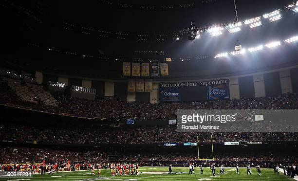 Players from the Baltimore Ravens and the San Francisco 49ers stand on the field as play was suspended due to a 34 minute power outage in the third...