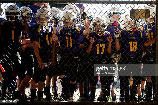 Players from the City of Fort Collins recreational league 6th grade team Vikings look through a fence as they prepare to play at halftime during the...