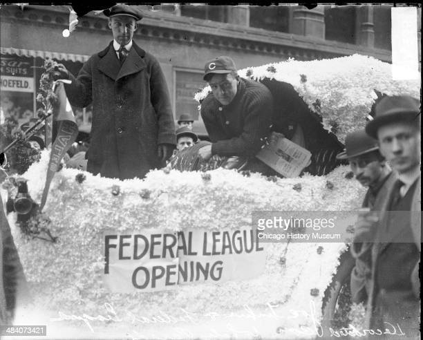 Players from the Federal League's Chicago Whales baseball team riding in an automobile covered with banners and light colored decorations in an auto...