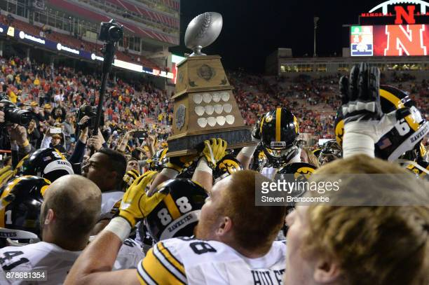 Players from the Iowa Hawkeyes hold aloft the Heroes Game Trophy after the win against the Nebraska Cornhuskers at Memorial Stadium on November 24...