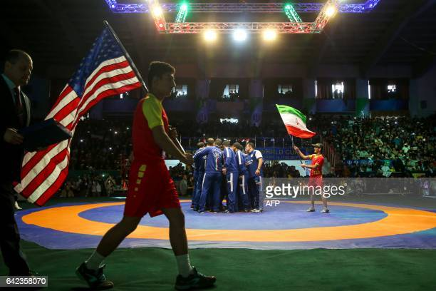 Players from the Iran and USA wrestling teams carry the flags of their respective nations prior to the start of the World Wrestling Cup Final in the...
