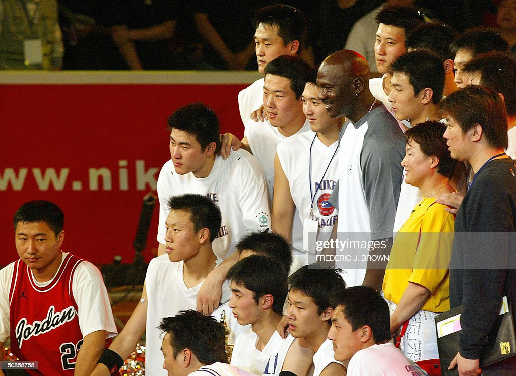 Players from the jubilant Shenyang #31 High School pose for a photo with US basketball legend Michael Jordan after he presented them a trophy for China's High School championship, 20 May 2004, at the Worker's Stadium Gymnasium in Beijing. Despite being a no show at open public events in the Chinese capital yesterday, Jordan's slick promotional tour has grabbed more headlines than the return to China of the nation's homegrown NBA hero Yao Ming. Shenyang's #31 High School defeated Shanghai's Nanyang Model High School for the championship. AFP PHOTO/Frederic J. BROWN