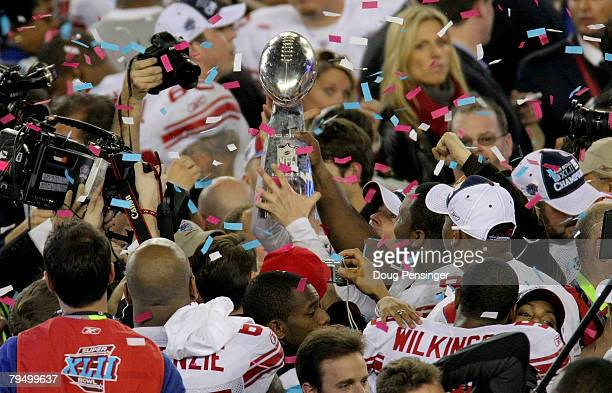 Players from the New York Giants celebrate with the Vince Lombardi trophy following their 17-14 win against the New England Patriots during Super...