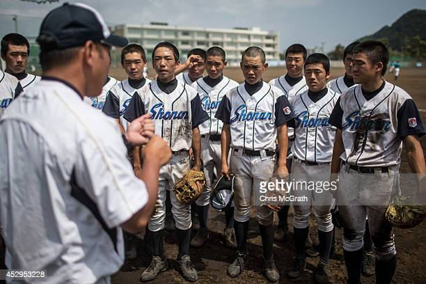 Players from the Shonan Boys listen to instructions from their manager during a practice game between the Shonan Boys and the Yokohama Minami on July...