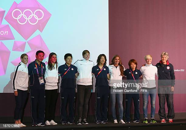 Players from the USA and Japan pose for the media during the Women's Football Final press conference at the Main Press Centre as part of the London...