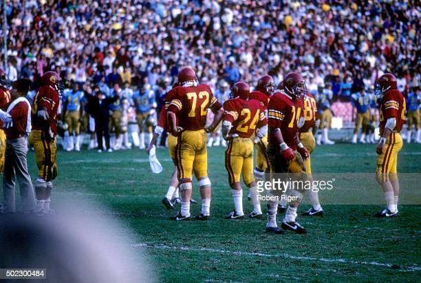 Players from the USC Trojans stand on the field against the UCLA Bruins during an NCAA game on November 20, 1982 at the Rose Bowl in Pasadena,...