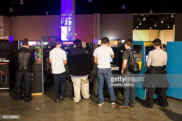 Players gather around an arcade machines at MAGfest 13 in National Harbor Md on January 24 2015 MAGfest is an annual convention held in the...