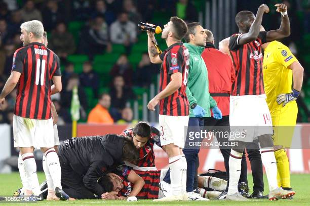 Players gather as AC Milan's Argentinian defender Mateo Musacchio receives medical attention during the Europa League group F football match between...