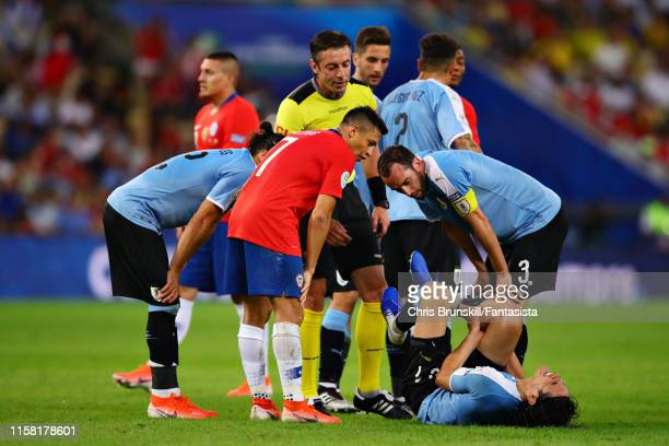 Players gather as Edinson Cavani of Uruguay reacts after a challenge during the Copa America Brazil 2019 group C match between Chile and Uruguay at...