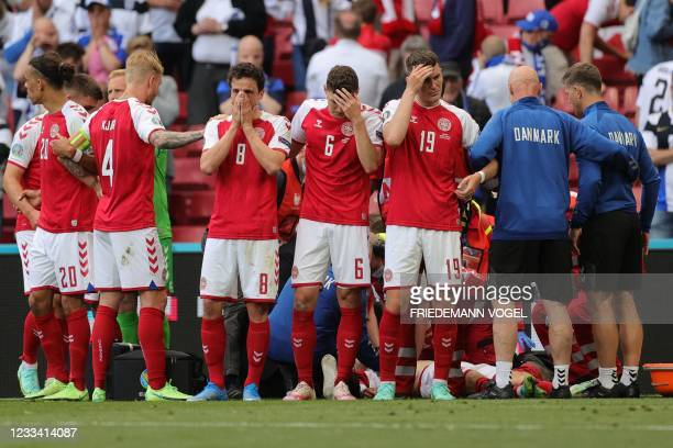 Players gather as paramedics attend to Denmark's midfielder Christian Eriksen during the UEFA EURO 2020 Group B football match between Denmark and...