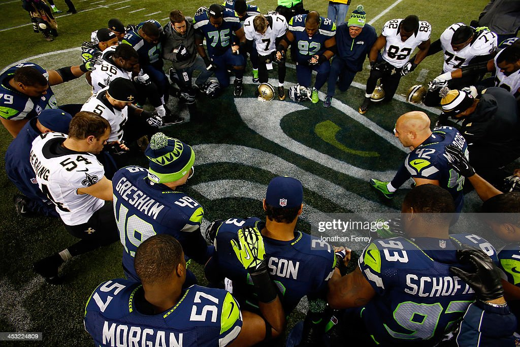 Players gather for a prayer on the field after the Seattle Seahawks defeated the New Orleans Saints 34-7 in a game at CenturyLink Field on December 2, 2013 in Seattle, Washington.