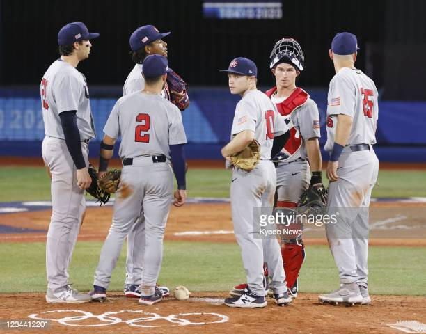 Players gather on the mound in the 10th inning of their Tokyo Olympic second-round game against Japan at Yokohama baseball stadium near Tokyo on Aug....