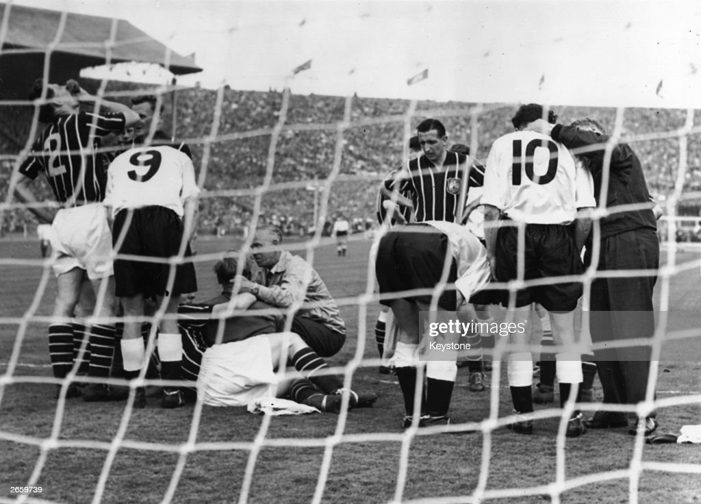 Players gather round the goal mouth as Manchester City's goalie, Bert Trautmann, receives medical attention to his neck, during the FA cup final against Birmingham City at Wembley. Manchester City won 3-1.