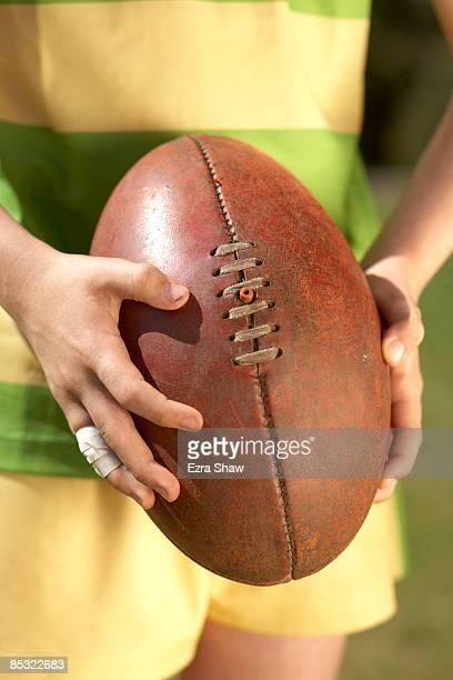 Players hands holding Australian football