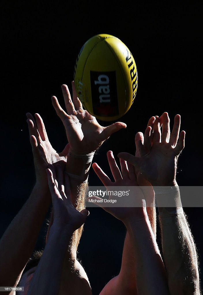 Players hands reach up for the ball during the round one NAB Cup AFL match between the West Coast Eagles and the Geelong Cats at Patersons Stadium on February 16, 2013 in Perth, Australia.