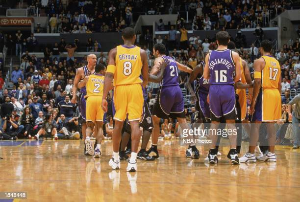 Players help to separate Rick Fox of the Los Angeles Lakers and Doug Christie of the Sacramento Kings after a first quarter altercation during the...