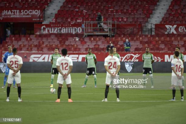 Players hold a minute of silence for coronavirus victims before the Spanish League football match between Sevilla FC and Real Betis at the Ramon...