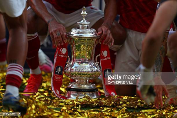 TOPSHOT Players hold the winner's trophy as the team celebrates victory after the English FA Cup final football match between Arsenal and Chelsea at...