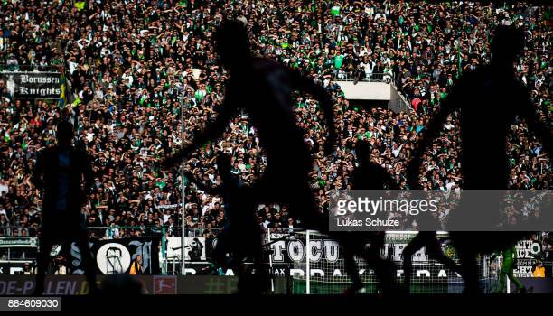 Players in action in front of a bright wall of fans during the Bundesliga match between Borussia Moenchengladbach and Bayer 04 Leverkusen at...
