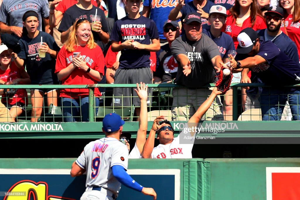 Players in the Boston Red Sox bullpen attempt to catch a two-run home run ball hit by Brock Holt #12 of the Boston Red Sox as Brandon Nimmo #9 of the New York Mets looks on in the third inning of a game at Fenway Park on September 16, 2018 in Boston, Massachusetts.