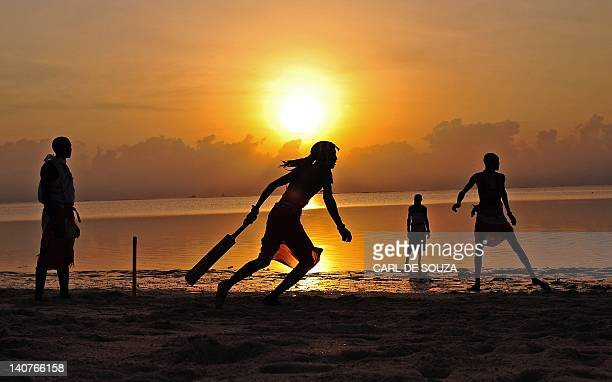 Players in the Maasai Warriors cricket team are silhouetted as they plays cricket on the beach in Mombasa South East Kenya on March 6 2012 The team...