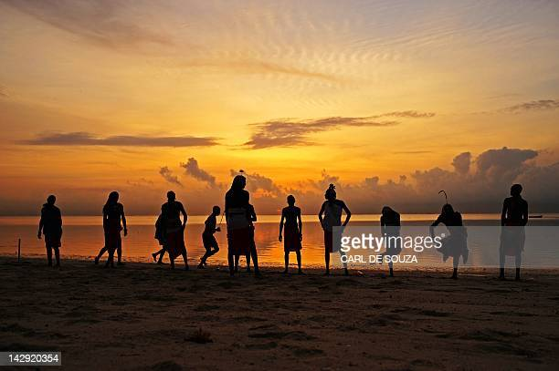 Players in the Maasai Warriors cricket team are silhouetted as they warm up before pratice at the beach in Mombassa South East Kenya on March 6 2012...