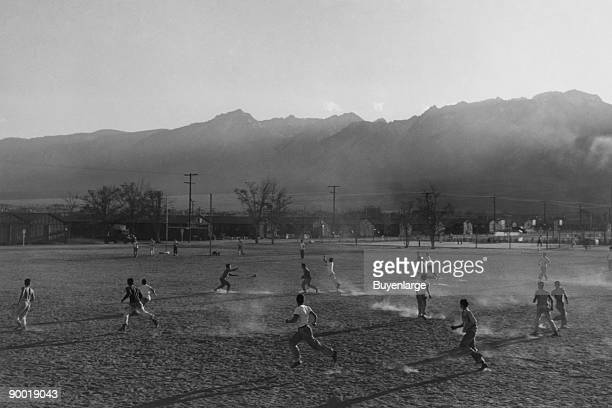 Players involved in a football game on a dusty field buildings and mountains in the distance Ansel Easton Adams was an American photographer best...