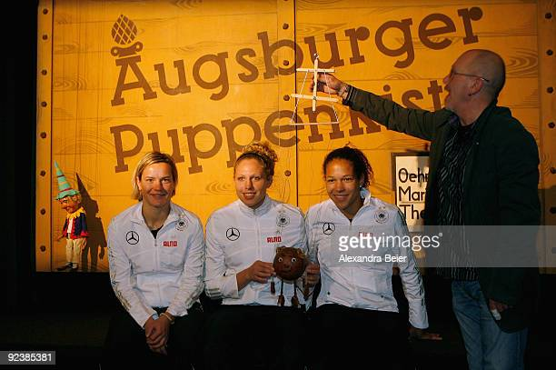 Players Jennifer Zietz Kim Kulig and Celia Okoyino da Mbabi of the women's German national soccer team pose with marionettes and a marionette player...
