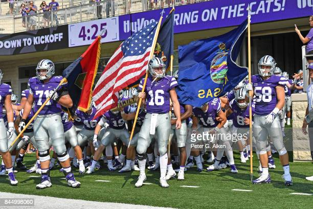 Players Jesse Ertz Dalton Risner and Breontae Matthews of the Kansas State Wildcats gets set to lead the Wildcats out onto the field against the...