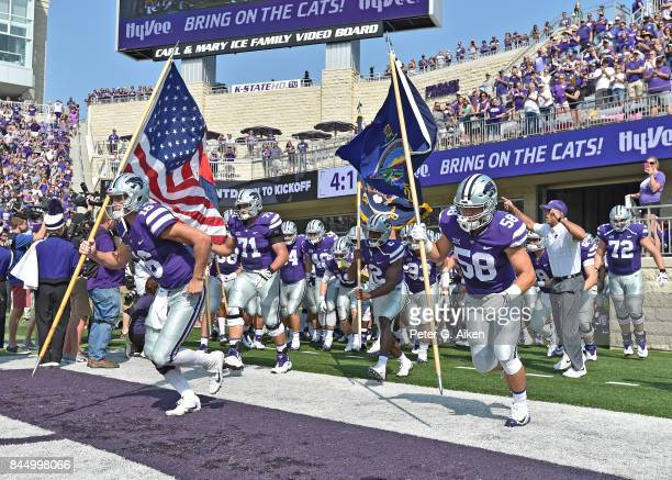 Players Jesse Ertz Dalton Risner and Breontae Matthews of the Kansas State Wildcats lead the Wildcats out onto the field against the Charlotte 49ers...
