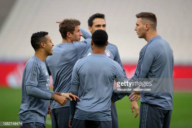 Players joke with Niklas Suele of FC Bayern Muenchen during a training session ahead of their UEFA Champions League Group E match against AEK Athens...
