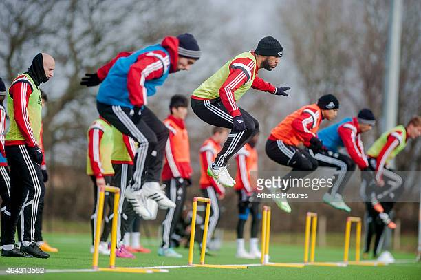 Players jump over hurdles during the Swansea City training session on February 24 2015 in Swansea Wales