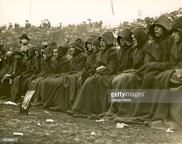 players keep warm on bench at football g - old american football stock photos and pictures